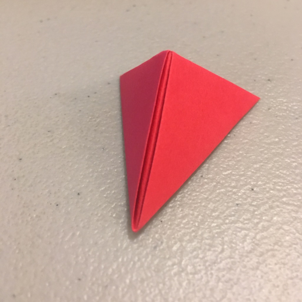 A red piece of paper folded into a triangular shape.